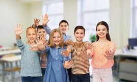 Happy students waving hands at school royalty free stock photos