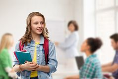 Happy smiling teenage student girl with school bag. Education, school and people concept - happy smiling teenage student girl with bag and books over classroom royalty free stock photography