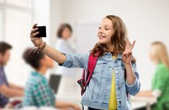 Teenage student girl taking selfie by smartphone. Education, school and people concept - happy smiling teenage student girl with bag taking selfie by smartphone royalty free stock photo