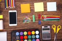 Education, school supplies, close up of stationery and smartphon Stock Image