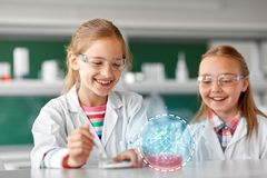 Kids making chemical experiment at school lab. Education, science, chemistry and children concept - kids or students making chemical experiment at school stock photos