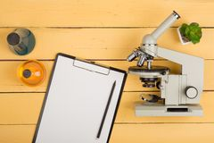 Science concept - microscope, blank clipboard and chemical liquids on the yellow desk in the auditorium. Education and science concept - microscope, blank stock image