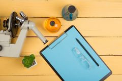 Science concept - microscope, blank clipboard, eyeglasses and chemical liquids on the yellow desk in the auditorium. Education and science concept - microscope stock image