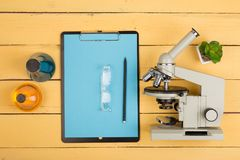 Education concept - microscope, blank clipboard, eyeglasses and chemical liquids on the yellow desk in the auditorium. Education and science concept - microscope royalty free stock photo