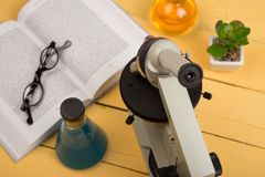 Science concept - microscope, book, eyeglasses and chemical liquids on the yellow desk in the auditorium. Education and science concept - microscope, book stock image