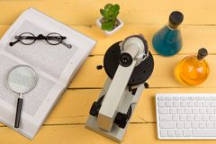 Education and science concept - microscope, book, magnifying gla. Ss, computer keyboard, eyeglasses and chemical liquids on the yellow desk in the auditorium Stock Images