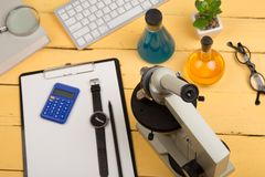 Education and science concept - microscope, book, magnifying glass, calculator, watch, blank clipboard, computer keyboard, eyeglas. Ses and chemical liquids on Stock Photography