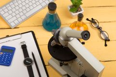 Education and science concept - microscope, book, magnifying glass, calculator, watch, blank clipboard, computer keyboard, eyeglas. Ses and chemical liquids on Stock Photo