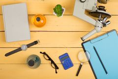 Education and science concept - microscope, book, magnifying glass, calculator, watch, blank clipboard, eyeglasses and chemical li. Quids on the yellow desk in royalty free stock images