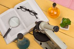 Education and science concept - microscope, book, magnifying glass, eyeglasses and chemical liquids on the yellow desk in the audi. Torium stock photography