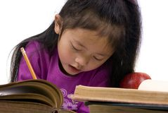 Education Series (writing). A young girl writes her letters with a pile of open books in the forground Royalty Free Stock Photography