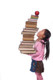 Education  (sky high books). The power of the future is your education. A young girl hold a tall tower of books. The weight of education Royalty Free Stock Photo