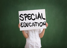 Education for those with special needs. Boy holding a sign with special education text written on white table Royalty Free Stock Image