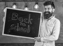 Education and studying concept. Teacher in eyeglasses holds blackboard with title back to school. Man with beard and. Mustache on happy face welcomes students stock photo