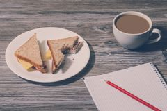 Education studying snack business essay composition hungry concept. Close up of bitten cheese sandwich, cup of hot coffee, open no stock photos