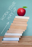 Education success. Large pile of books against a blackboard with an upwards arrow stock image