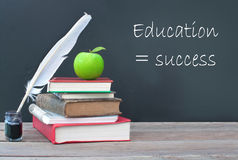 Education is success. Education success written on a blackboard with a pile of books, quill and ink Royalty Free Stock Images