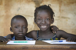 Education Symbol: Couple of African Children Smiling at School. Back To School Symbol - African Girl Toothy Huge Smile Showing Red Pencil Stock Photo