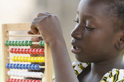 Education symbol: Little African girl learning to count. Little african girl counting on abacus frame on blurred background Stock Photo
