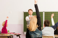 Education - Teacher with pupil in school teaching Stock Photos