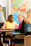 Education - Teacher with pupil in school teaching Stock Photo