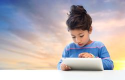 Little girl with tablet pc over evening sky. Education, technology and childhood concept - little girl with tablet pc computer over evening sky background Stock Images