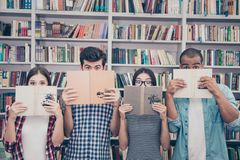 Education and teenage concept. Group of four muiti ethnic students in casual outfits are hiding behind the open books, with wide. Open eyes, surprised stock image