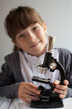 Education. Teenage girl studying science with microscope Stock Image