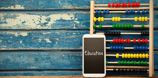 Composite image of education text against white background. Education text against white background against smart phone with abacus on table stock illustration