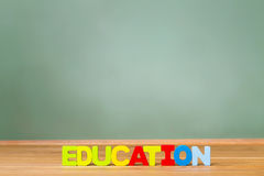 Education theme with big wood blocks and green chalkboard Stock Photos