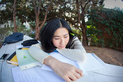 Education is tiresome. Sad young Asian girl laying on a pile of books and papers Stock Photo