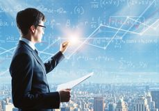 Education and tutor concept. Side portrait of handsome young businessman writing mathematical formulas on bright city background. Education and tutor concept Royalty Free Stock Photography