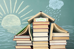 Education. Unusual education concept. School from books on background of chalk drawing of sun and rain Stock Photo
