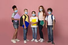 Education during virus outbreak. Diverse children with schoolbags and notebooks wearing masks on pink background