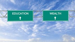 Education and wealth. Road sign to education and wealth Stock Photo