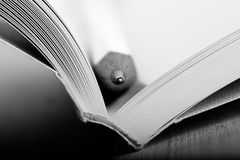Education and wisdom concept - Macro view of book with pencil stock image