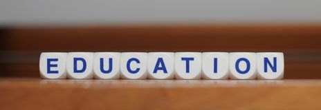Education. Word cubes on brown background Royalty Free Stock Photography