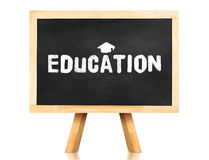 Education word and Graduation cap icon on blackboard with easel. And reflection on white background,Business concept Royalty Free Stock Photography