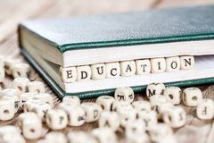 Education word written on a wooden block. Education word written on a wooden block in a book. On old wooden table Stock Image