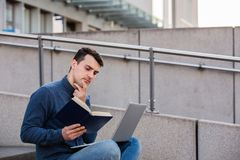 Education and working concept. Concentrated student preparing for an exam in campus area sitting on university stairs. Student man reading book and using  laptop stock photos