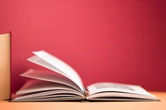 Education and reading concept. Open book on minimalistic red background stock images