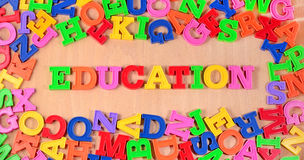 Education written by colorful letters on a wooden background Royalty Free Stock Images