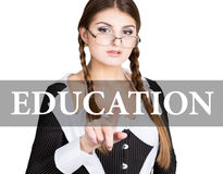 Education written on virtual screen. sexy secretary in a business suit with glasses, presses button on virtual screens Stock Image