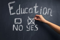 Education: yes or no. Human hand writes education yes on a blackboard Stock Photography