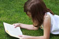Education.Young beautiful girl reading a book outdoor Stock Photo