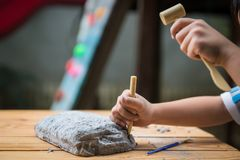 Educational archaeology toy. Kid playing with educational archaeology toy with dinosaur fossil stock photos