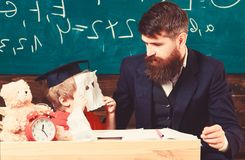 Educational concept. Handsome teacher and a small boy sitting in front of a green board. Kid in graduation cap hiding stock images