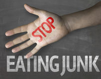 Educational and Creative composition with the message Stop Eating Junk on the blackboard Royalty Free Stock Images