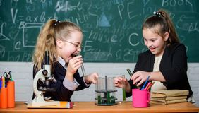 Educational experiment concept. Microscope and test tubes on table. Be careful performing chemical reaction. Basic. Knowledge of chemistry. Girls study stock photos