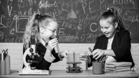 Educational experiment concept. Microscope and test tubes on table. Be careful performing chemical reaction. Basic. Knowledge of chemistry. Girls study royalty free stock images